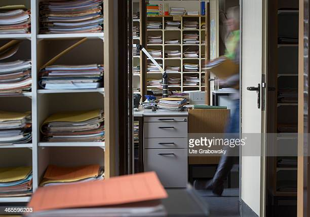 The blurred image of one of the administrative staff of the Tax and Revenue Office walking past the doorway of the office as pictured amongst shelves...