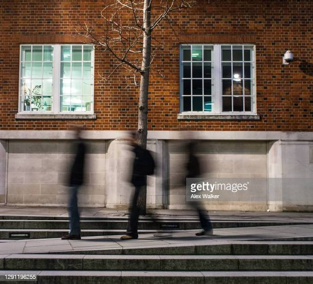 the blurred motion of commuters rushing at night - business security camera stock pictures, royalty-free photos & images