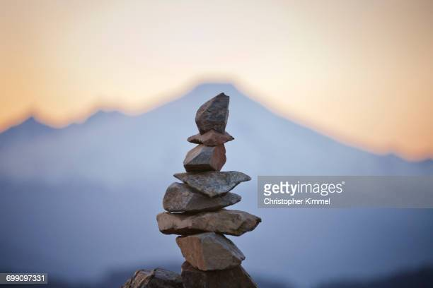 the blurred outline of mount baker frames a summit cairn. - 石塚 ストックフォトと画像