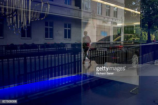 The BMW car showroom on Park Lane and reflections of the Mayfair street outside. A silhouetted figure walks behind the polished car that is featured...