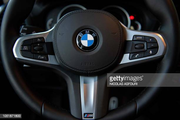 The BMW logo is seen on the steering wheel of a car at a BMW car dealership in Beijing on October 11 2018 German luxury carmaker BMW announced on...