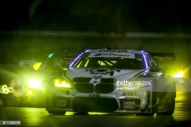 The BMW of Jens Klingmann of Germnay Martin Tomczyck of Germany Mark Kvamme Don Yount and Cameron Lawrence leads a pack of cars at night during the...