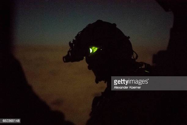 The board engineer of the NH90 Helicopter of the Bundeswehr the German Armed Forces observes the desert during a night training flight using night...