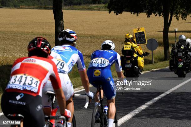 The board girl announces the time to Belgium's Julien Vermote France's Arthur Vichot and Belgium's Thomas De Gendt during the 2075 km fourth stage of...