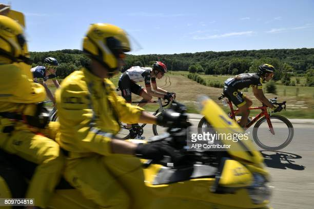 TOPSHOT The board girl rides past France's Perrig Quemeneur Norway's Vegard Laengen and Belgium's Frederik Backaert riding in a breakaway during the...
