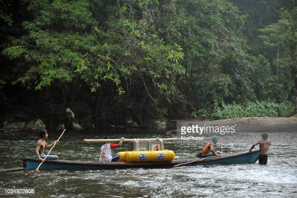 The boat carrying a cage containing orangutan crossing the Metatai river in Bukit Baka Bukit Raya National Park on September 122018 IAR together with...
