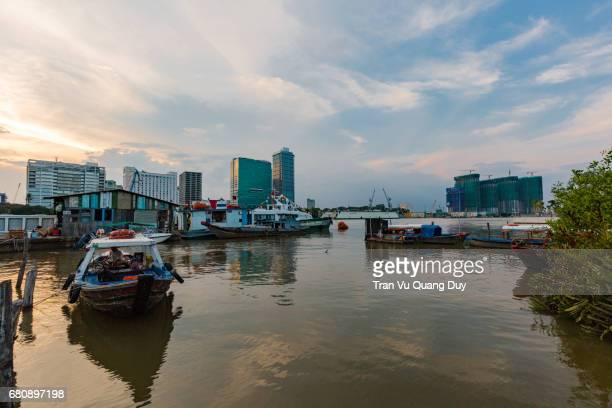 the boat is anchored at the bank of thu thiem river. - thiem foto e immagini stock