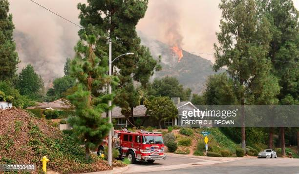 The Bobcat Fire burns on hillsides behind homes in Arcadia, California on September 13, 2020 prompting mandatory evacuations for residents of several...