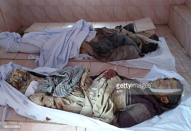 The bodies of Aghan civilians killed in a roadside bomb that ripped through a passenger bus lie on the ground in a hospital in Ghazni on September 10...