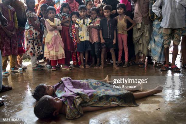 The bodies of children are seen as local children watch being prepared for the funeral after a boat sunk in rough seas off the coast of Bangladesh...