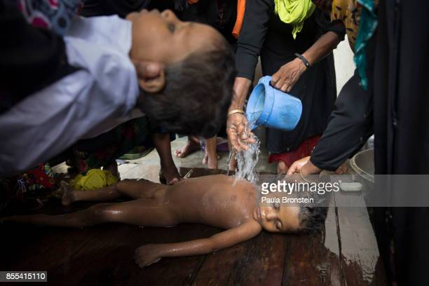 The bodies of children are washed by women in preparation for the funeral after a boat sunk in rough seas off the coast of Bangladesh carrying over...