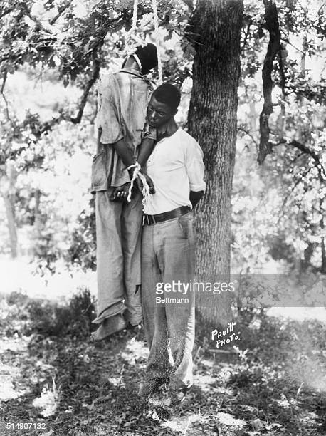 The bodies of Dooley Morton and Bert Moore of Lowndes County are shown hanging from a tree after the two were lynched by an angry mob of white...