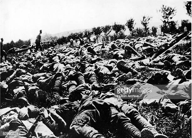 The bodies of hundreds of Italian soldiers lie dead on the battlefield victims of a gas and flame attack during World War I as others haul the...