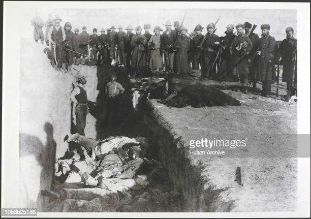 The bodies of Lakota Sioux being unceremoniously piled into a mass grave hacked into the frozen Dakota soil after the massacre at Wounded Knee South...