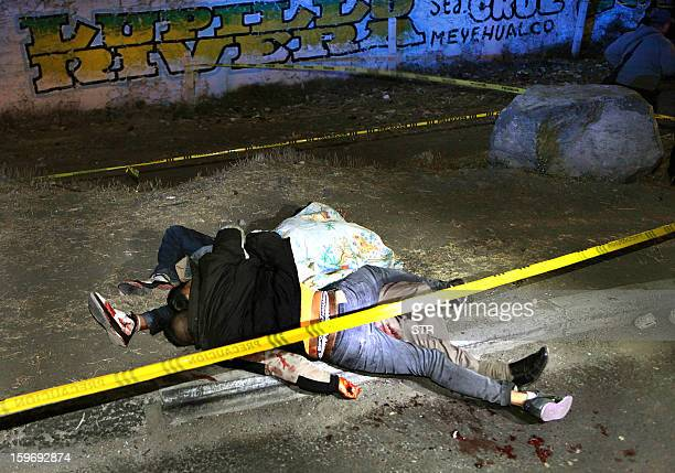 The bodies of three Mexican youngsters lie on MexicoPuebla highway after being shot by unknown men on January 17 2013 at the Emiliano Zapata...