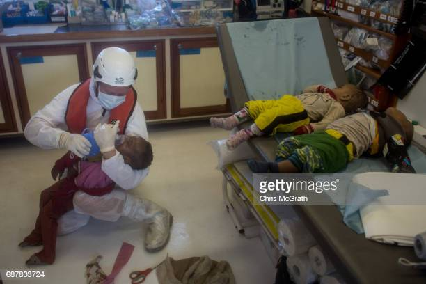 The bodies of two babies are seen on a table as a paramedic tries to save the life of a third child who later died after they were pulled from the...