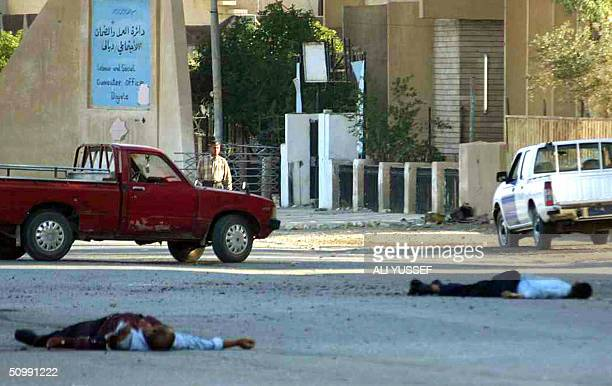The bodies of two policemen lie dead on the floor close to a police station in Baquba 60 kms northeast of Baghdad 24 June 2004 Eighteen people...