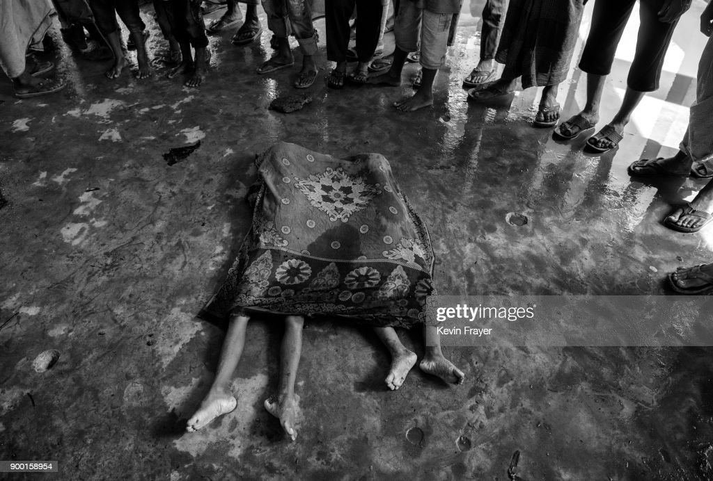 "COX'S BAZAR, BANGLADESH - SEPTEMBER 29:The bodies of two Rohingya refugee children are seen covered prior to burial after a boat capsized killing dozens while fleeing Myanmar on September 29, 2017 in Cox's Bazar, Bangladesh. More than half a million Rohingya refugees have flooded into Bangladesh to flee an offensive by Myanmar's military that the United Nations has called ""a textbook example of ethnic cleansing"". The refugee population is expected to swell further, with thousands more Rohingya Muslims said to be making the perilous journey on foot toward the border, or paying smugglers to take them across by water in wooden boats. Hundreds are known to have died trying to escape, and survivors arrive with horrifying accounts of villages burned, women raped, and scores killed in the ""clearance operations"" by Myanmar's army and Buddhist mobs that were sparked by militant attacks on security posts in Rakhine state on August 25, 2017. What the Rohingya refugees flee to is a different kind of suffering in sprawling makeshift camps rife with fears of malnutrition, cholera, and other diseases. Aid organizations are struggling to keep pace with the scale of need and the staggering number of them — an estimated 60 percent — who are children arriving alone. Bangladesh, whose acceptance of the refugees has been praised by humanitarian officials for saving lives, has urged the creation of an internationally-recognized ""safe zone"" where refugees can return, though Rohingya Muslims have long been persecuted in predominantly Buddhist Myanmar. World leaders are still debating how to confront the country and its de facto leader, Aung San Suu Kyi, a Nobel Peace Prize laureate who championed democracy, but now appears unable or unwilling to stop the army's brutal crackdown."