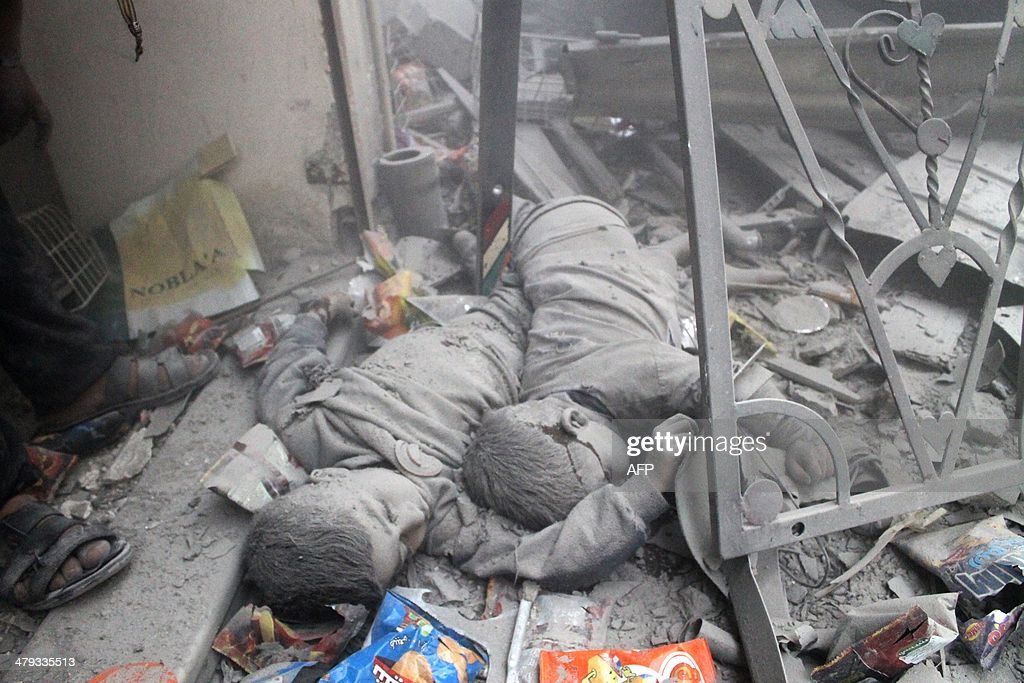 The bodies of two Syrian children lie in the rubble of a residential building reportedly hit by an explosives-filled barrel dropped by a government forces helicopter on March 18, 2014.