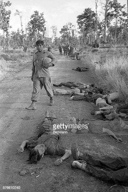 The bodies of Viet Cong soldiers lie on a road following a fierce fight near An Loc about 90 miles north of Saigon The Viet Cong regiment was cut to...