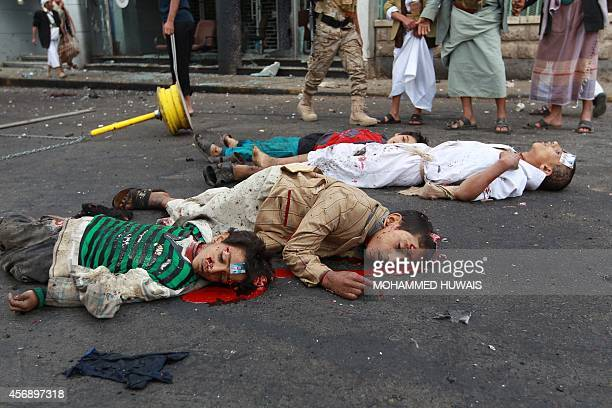 The bodies of Yemeni youths lie on the ground after a powerful suicide bombing rocked the Yemeni capital Sanaa on October 9 2014 leaving at least 32...