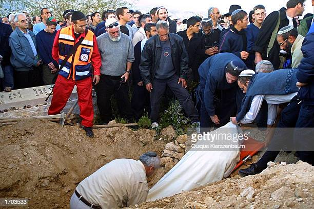 The body of 17yearold Gabriel Hoter is placed in a grave December 29 2002 after his funeral in the Jewish settlement of Kfar Adumim in the West Bank...