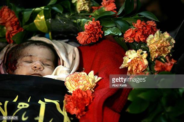 The body of 18 daysold newborn Palestinian baby girl Amira Abu Asr lies amidst flowers at her family home during her funeral March 5 in Gaza city...