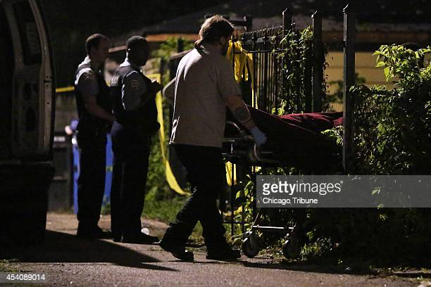 The body of a 33yearold man is removed from the scene where three people were shot in the early morning hours on Sunday Aug 24 in the North Austin...