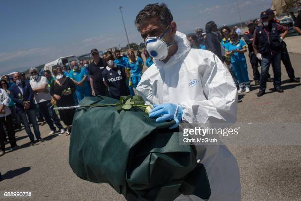 The body of a a small child that died at sea on May 24th is carried off the Migrant Offshore Aid Station 'Phoenix' vessel by Italian forensic teams...