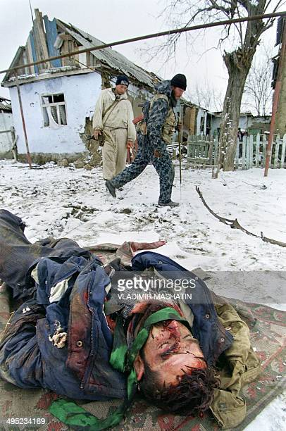 The body of a Chechen fighter lies on the ground 19 January 1996 in the village of Pervomaiskaya taken by assault by Russian soldiers after four days...