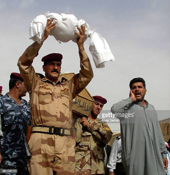 The body of a child killed with his family northeast of Baghdad is carried to the burial by an Iraqi army officer on November 7 2005 in the holy...