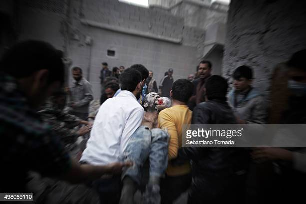 The body of a civilian is rushed away from the scene a regime airstrike that leveled a large part of one of Aleppo's residential neighborhoods March...