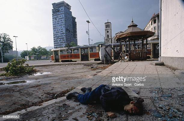 The body of a civilian victim of the siege of Sarajevo lies on a sidewalk, surrounded by broken glass, during the Yugoslavian Civil War. The siege of...