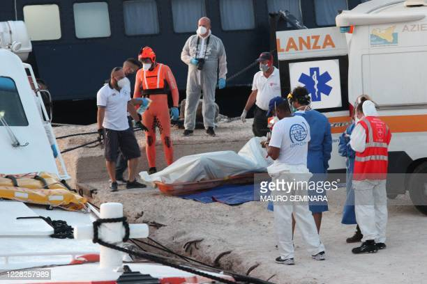 The body of a dead migrant wrapped in a blue bag is being put into an ambulance, after some 49 rescued migrants arrived at the commercial port of...