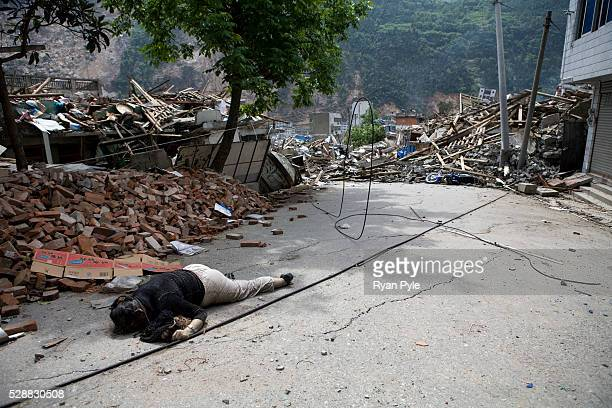 The body of a dead woman lay in the street in the completely destroyed city of Beichuan Sichuan China A 79 magnitude earthquake that struck China's...
