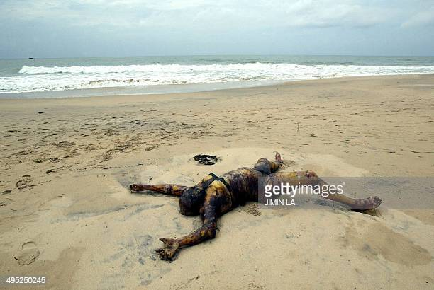 The body of a dead woman lies on a beach after tidal waves crashed onto land in Sinigame near the tourist town of Hikaduwa on the southwestern coast...