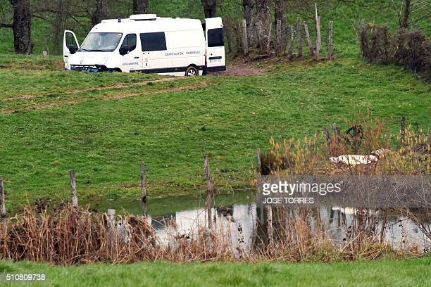The body of a dead young woman is pictured next to a pond near a police van of the criminal identification at a dairy farm in Mayran on February 17...