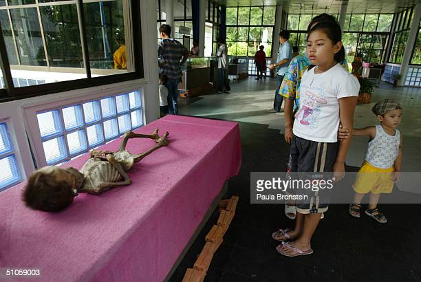 The body of a fiveyearold AIDS victim lies on a table at the 'Life Museum' at the Wat Phrabaht Nampu AIDS hospice July 14 2004 in Lopuri Thailand The...