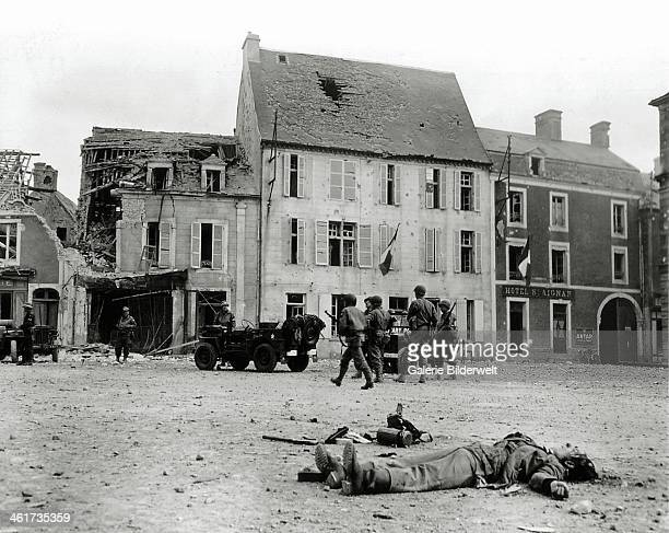 The body of a German soldier belonging to the 2 Infanterie Regiment is lying on the Market Square 15th June 1944 The two jeeps in the center of the...