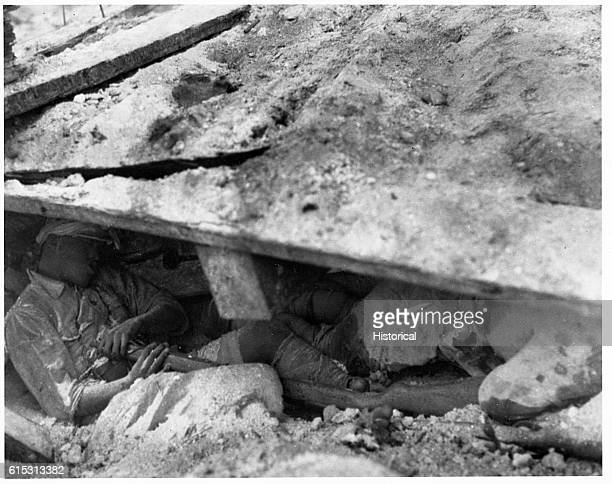 The body of a Japanese soldier who killed himself during the US Marines' conquest of Tarawa lies under a demolished dugout with the body of a comrade...