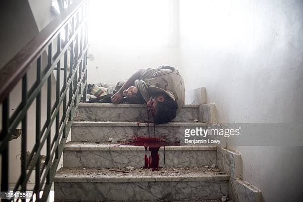 The body of a Libyan rebel lies on the floor of a cramped stairwell after being shot by a Gaddafi loyalist sniper hiding on the floor above in the...
