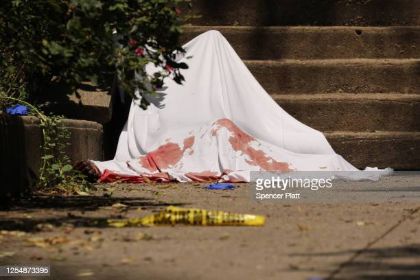 The body of a man lays under a white sheet at the scene of an afternoon shooting that left one person dead on July 07, 2020 in the Brooklyn borough...