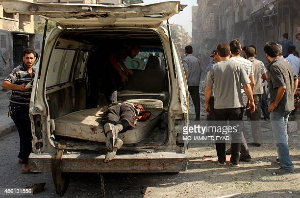 The body of a man lies in the back of van as residents and emergency personnel search for victims following Syrian government forces air strikes on a...