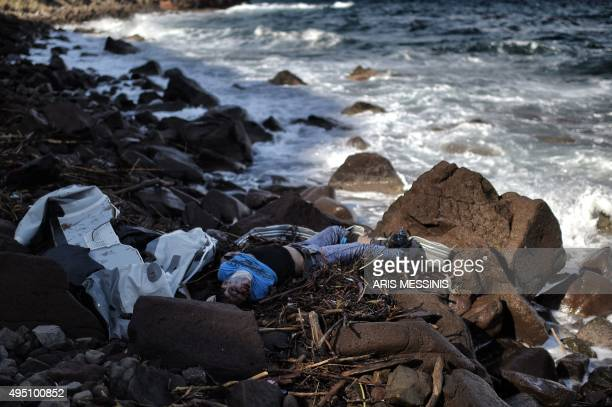 The body of a man lies on a beach on the Greek island of Lesbos on October 31 after boats transporting migrants and refugees trying to cross the...