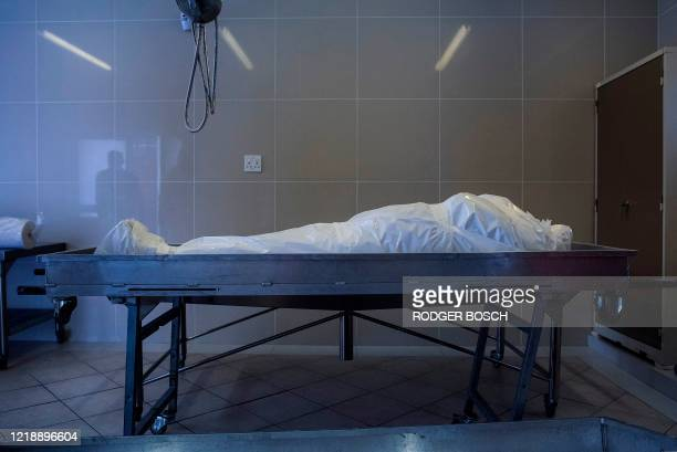 The body of a man who died of COVID-19 coronavirus lies waiting to be prepared for burial at the Ghietmatiel Islamia Mosque in Athlone, Cape Town, on...