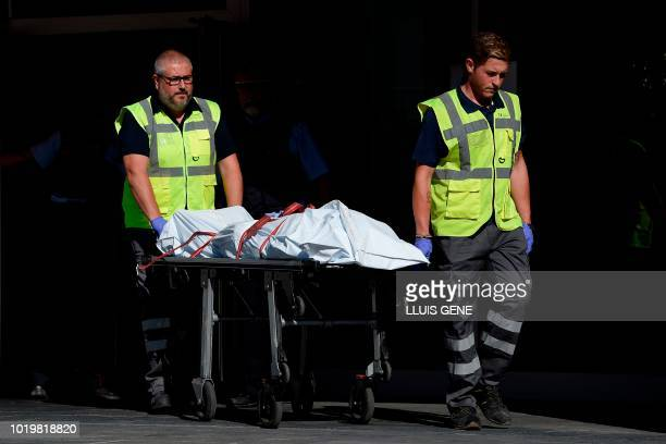 TOPSHOT The body of a man who tried to attack a police station is carried out of the premises in Cornella near the northeastern Spanish city of...