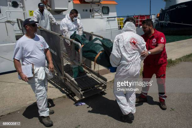 The body of a mirgant that died at sea attempting to reach Italy on May 24th is carried off the Migrant Offshore Aid Station 'Phoenix' vessel by...