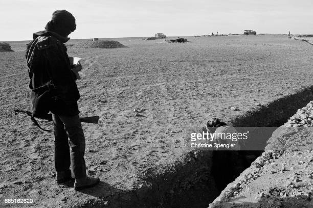 The body of a Moroccan killed during conflict with the Polisario Front lies in a trench as a Polisario soldier stands nearby in Mahbes Western Sahara...