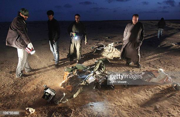 The body of a reported fighter pilot lies in the desert March 25 2011 near Ras Lanuf, Libya. Opposition forces claimed to have shot the Libyan...