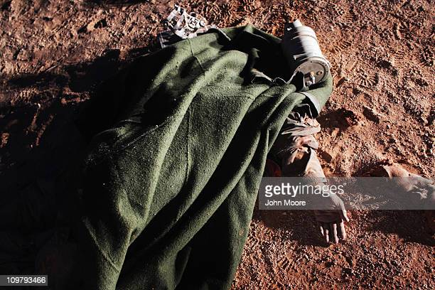 The body of a reported Libyan fighter pilot lies in the desert March 25 2011 near Ras Lanuf, Libya. Opposition forces pushed government troops...